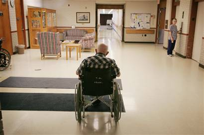 Old man sitting alone in wheelchair in a nursing home facility, viewed from behind