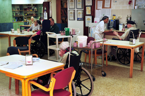 Nursing home patients in wheelchairs around tables