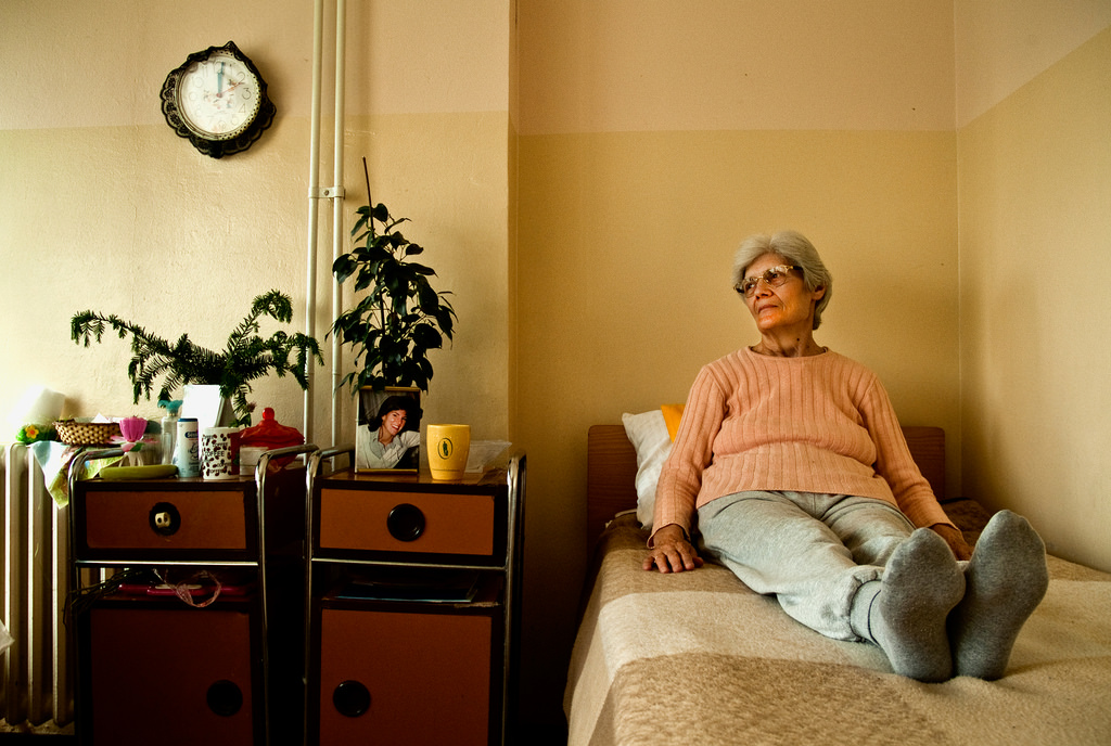 Elderly woman in an orange sweater sitting on her bed in a nursing home