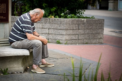 Sad-looking elderly man sitting on a stone bench outside