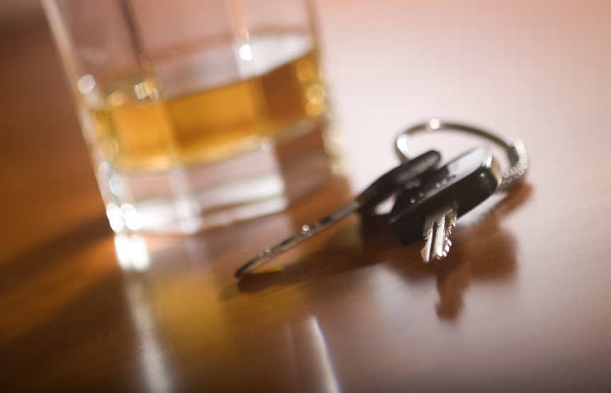 A glass of brown liquor next to car keys