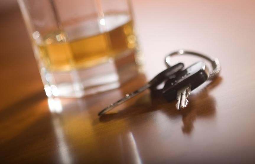A glass of brown liquor next to car keys