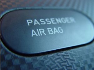 "Close up of a button on a car console labeled ""Passenger Air Bag"""