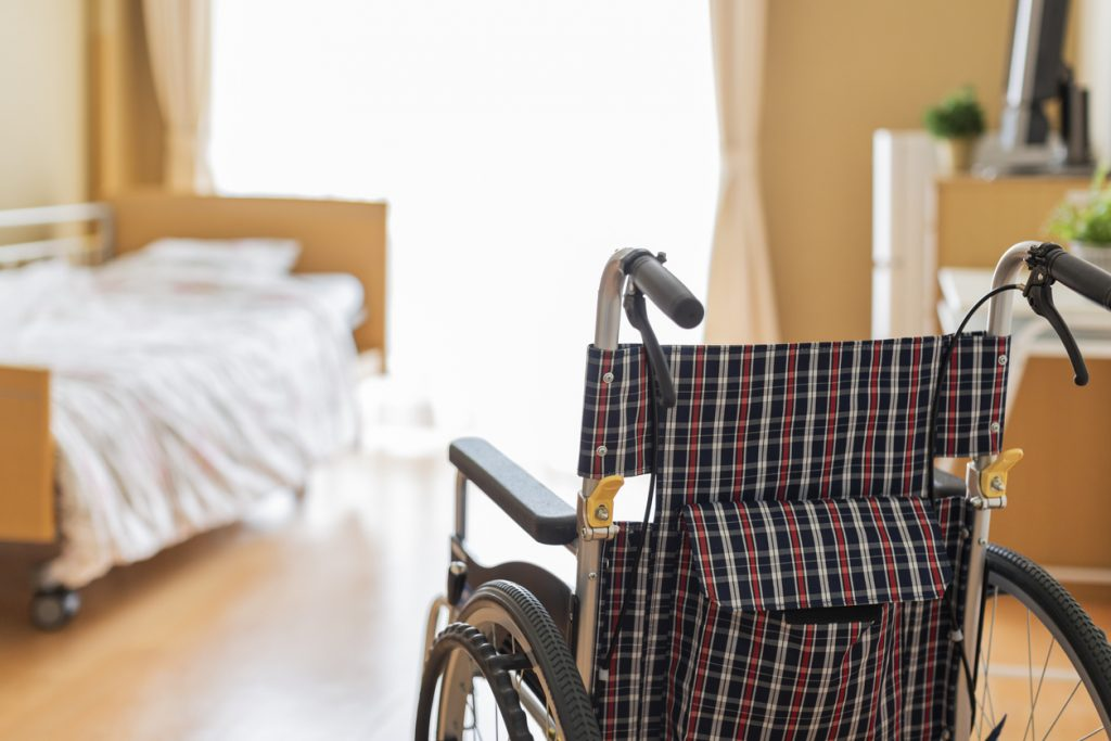 Wheelchair in front of unmade bed in nursing home