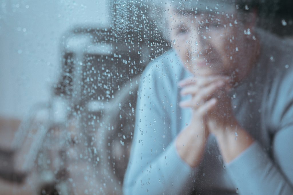 Elder lady with depression sitting alone looking out the window with raindrops on it