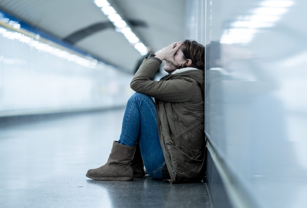 Young adult woman feeling shame depressed and hopeless sitting alone in a subway corridor.