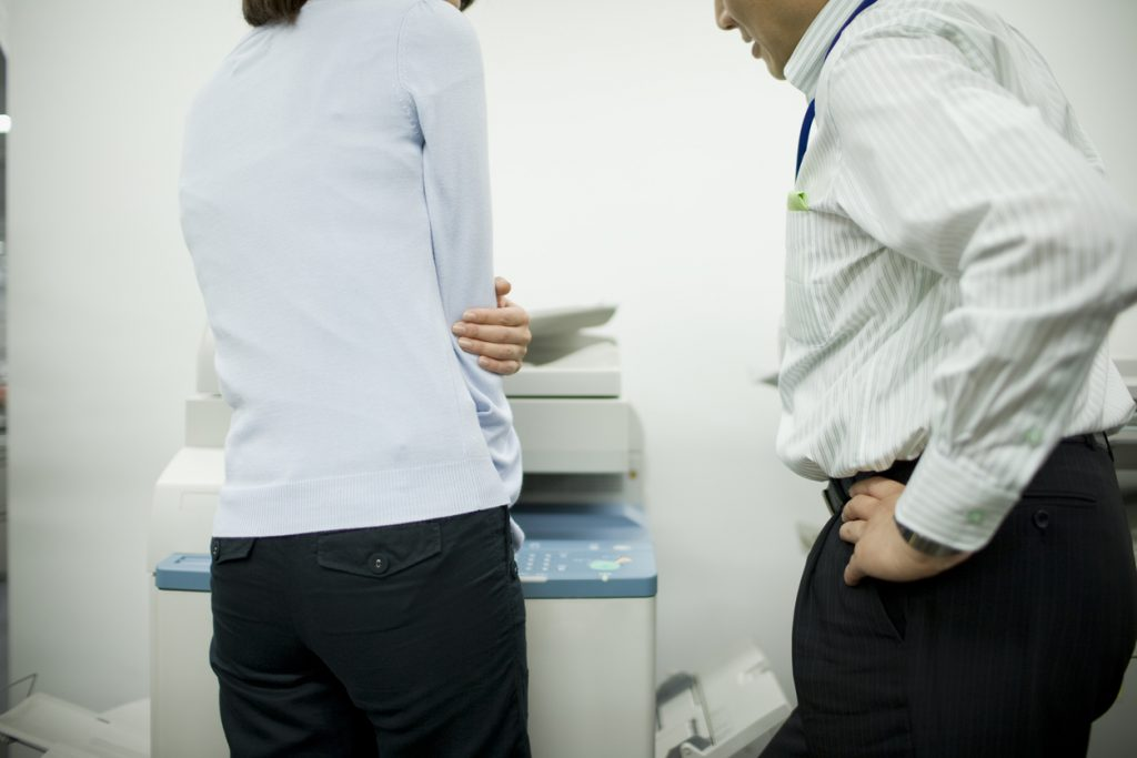Male boss talking to uncomfortable female subordinate in front of a copy machine