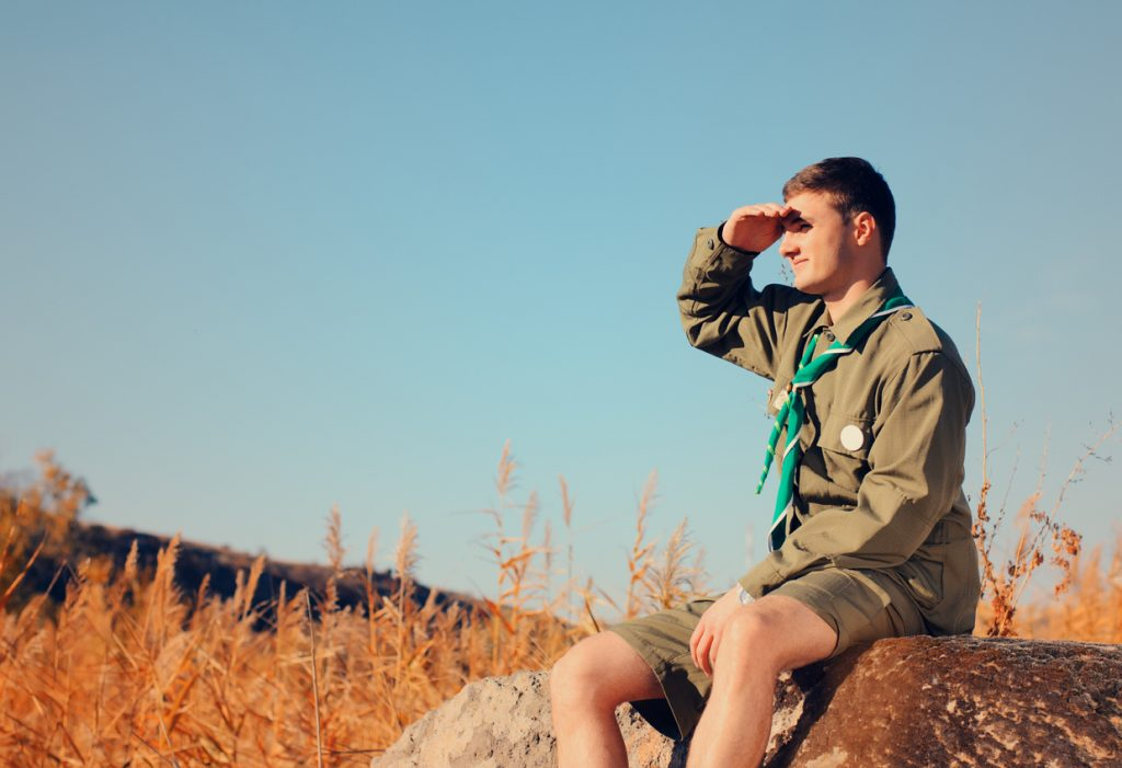 Young Boy Scout in Uniform Watching Over a Field on A Sunny Day While Sitting on a Boulder