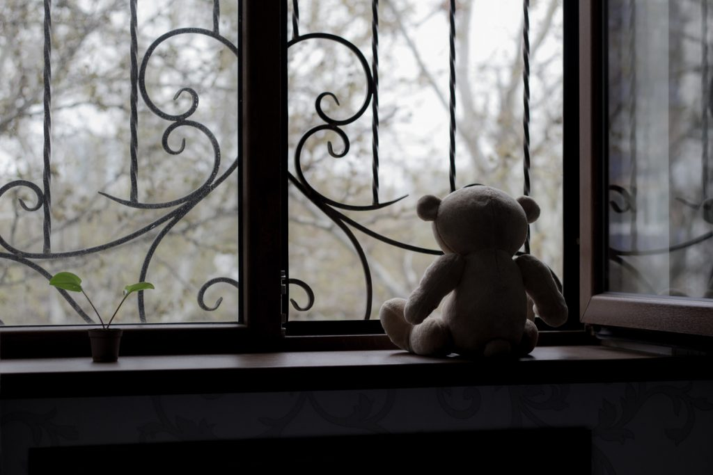 Teddy bear sitting on a windowsill facing the outside in a darkened room