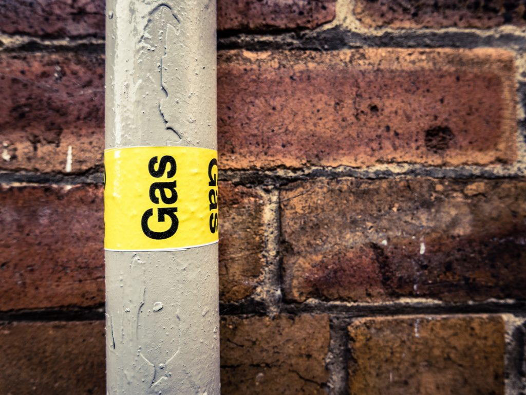"Detail Of A Residential Gas Pipe Against A Red Brick Wall with a yellow label marked ""GAS"""