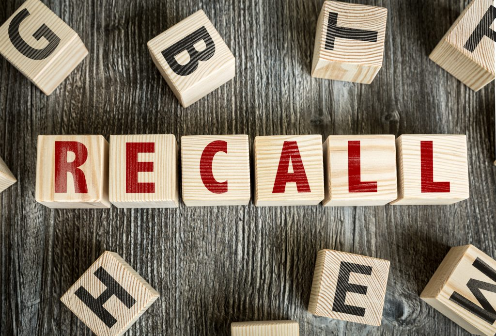"Wooden blocks with red letters spelling out the word ""recall"""