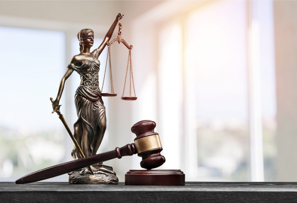 Small statue of lady justice next to a gavel in a courtroom