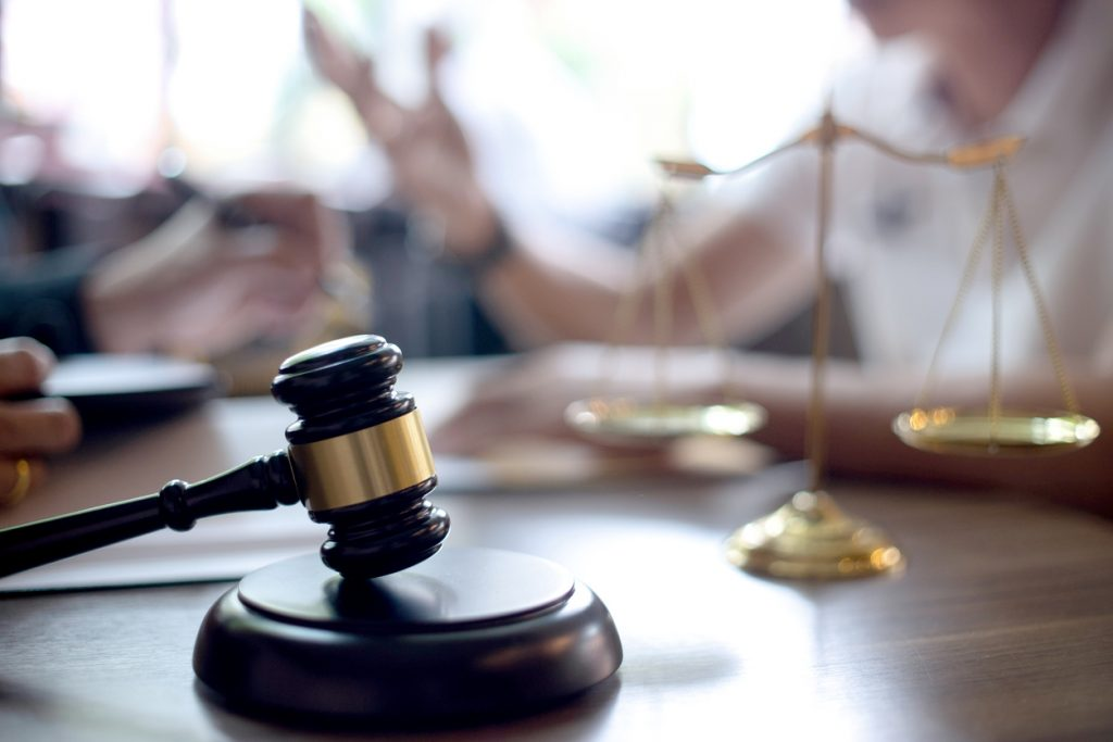 Lawyer and client meeting with a gavel and scales in the foreground