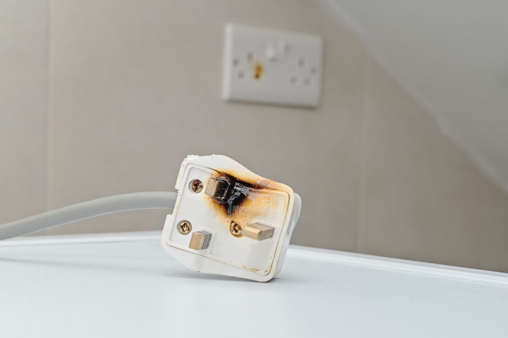 A burnt extension cord sitting on a white table.