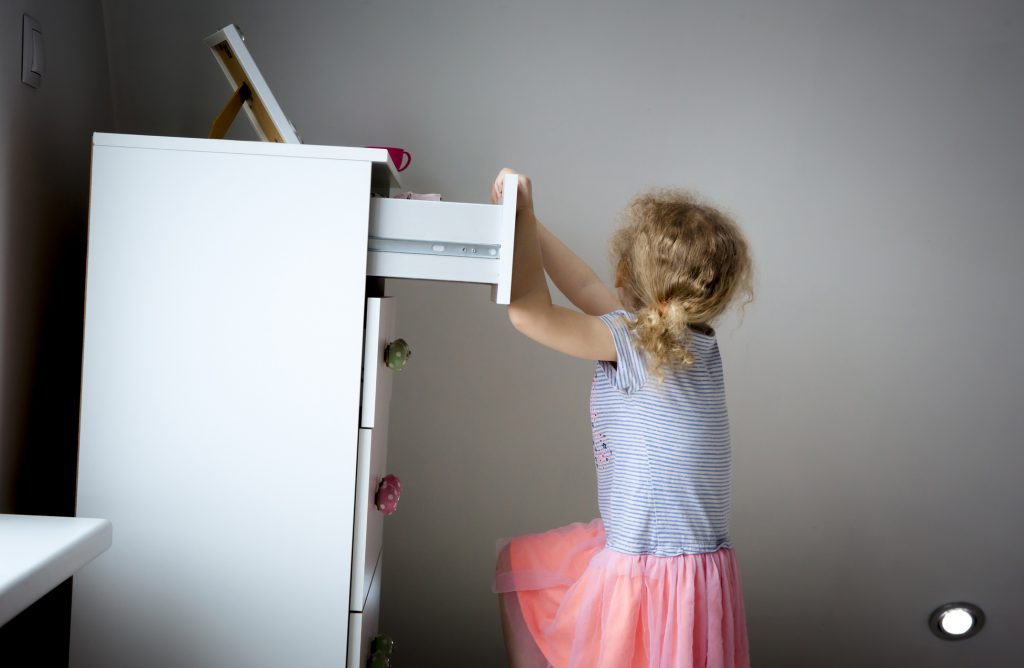 Young girl pulling on the top drawer of a dresser and tipping it over