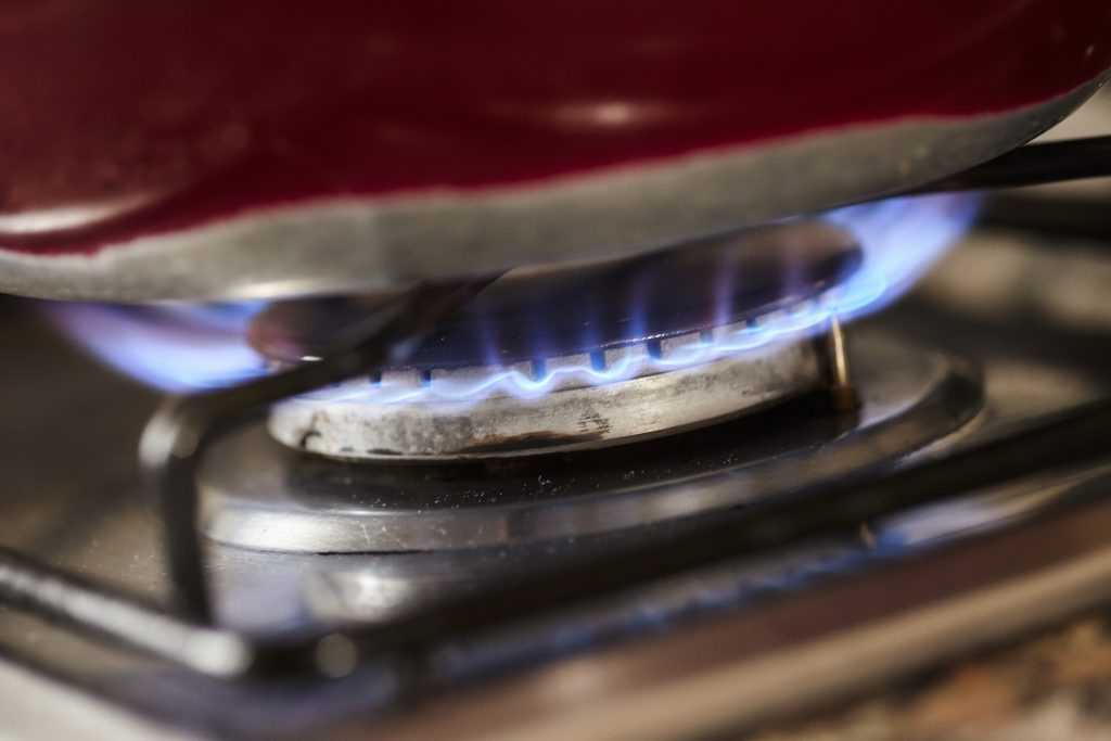 Detail of a gas stove lit with a blue flame