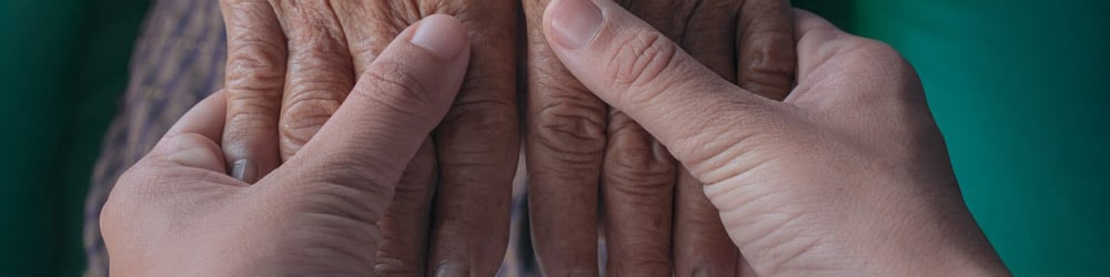Person holding an elderly person's hands