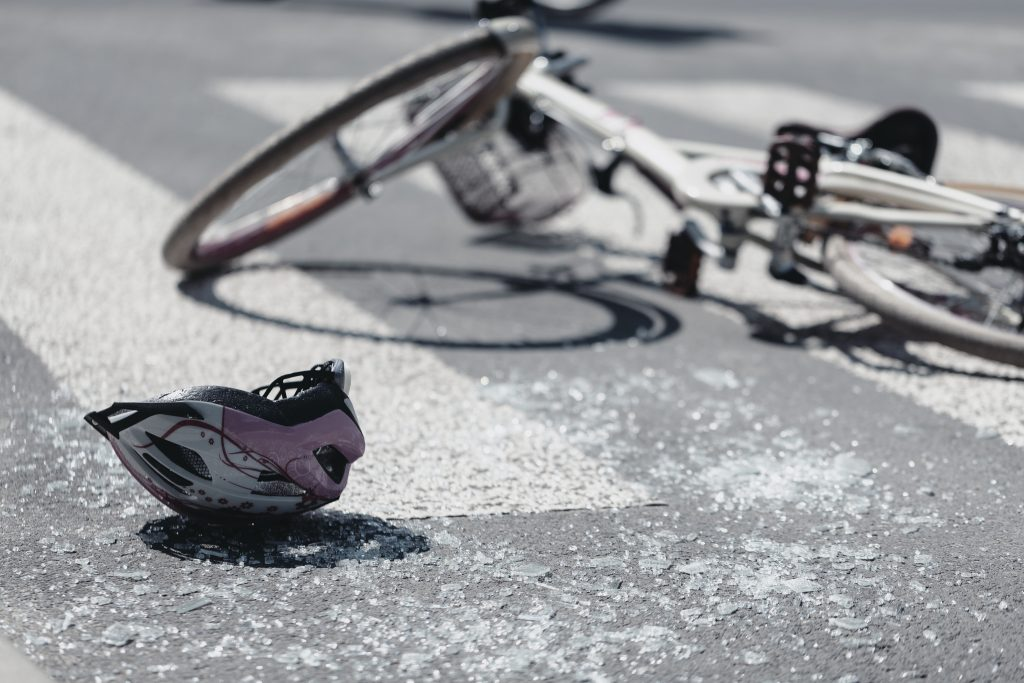 Helmet and bicycle laying in the street after accident