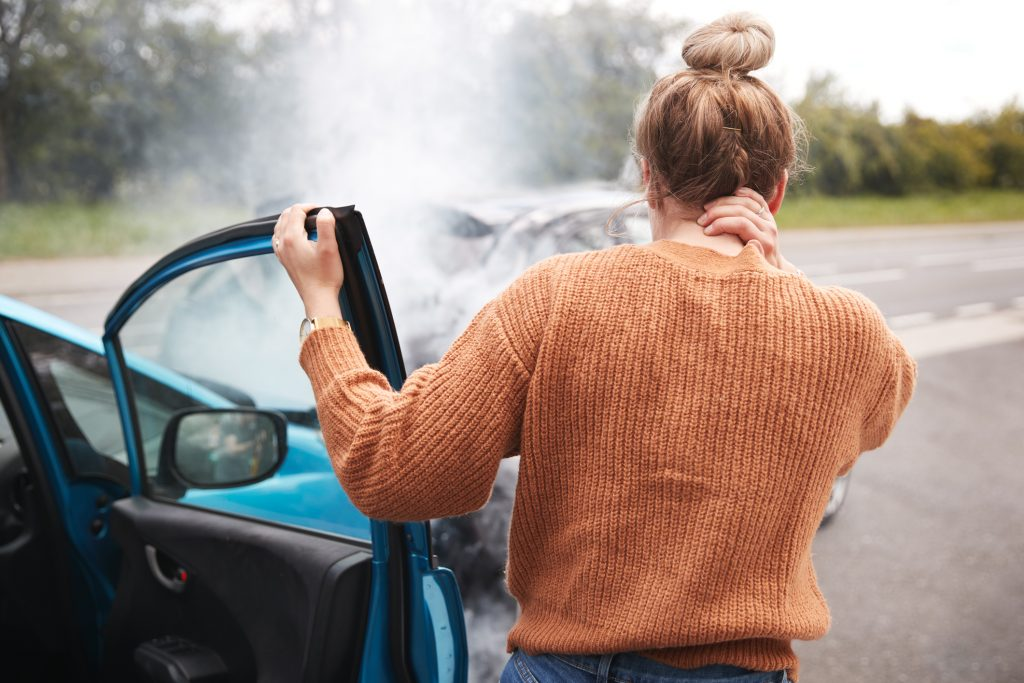 Woman standing by the door of a crashed car