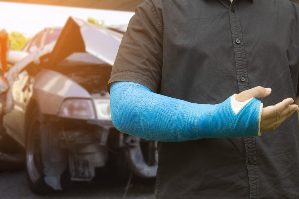 Man wearing an arm cast in front of a car wreck