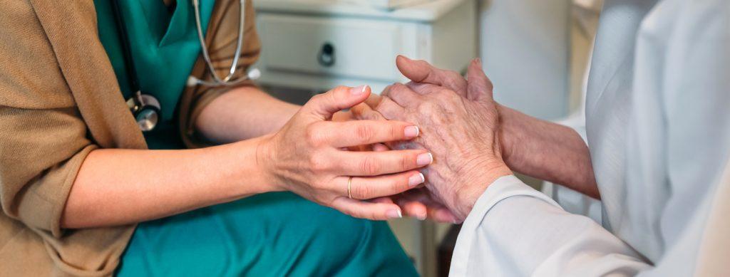 doctor holding an elderly woman's hands